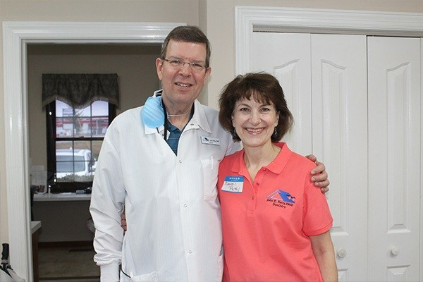 Dentist and team member smiling together
