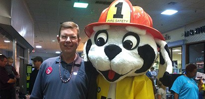 Dentist and fire dog mascot at community event