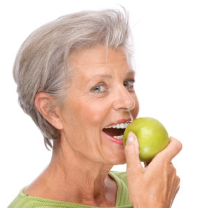 older woman smiling holding apple