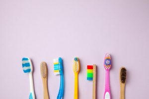 Several different colored toothbrushes on a table